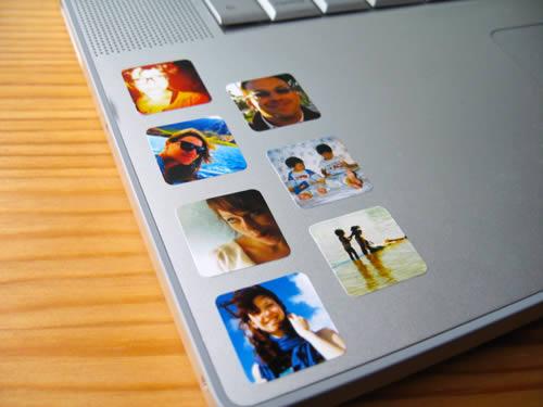 Vista parcial de teclado de laptop con pequeñas fotografías adheridas.