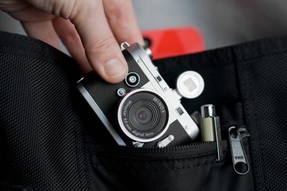 Mano guardando la mini cámara en un pequeño bolsillo.